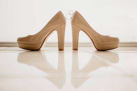 Gold wedding rings between pair of white high heel shoes. Wedding details on mirror floor near panoramic window.