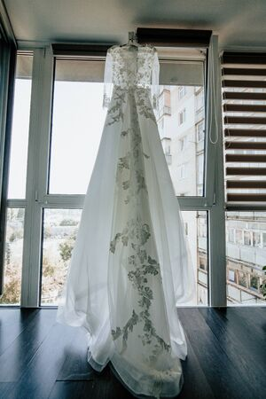 Wedding dress on hanger by the window in the bride room. On her wedding day.