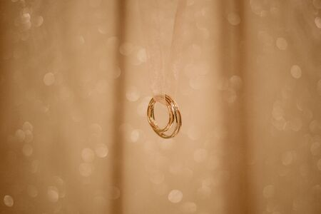Two golden wedding rings hanging on a ribbon, isolated on blurred background with light glares.