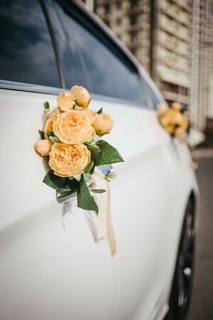Wedding decor on the car handle. Flower decoration with ribbons on a white car.