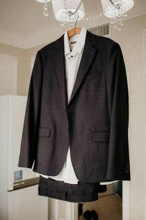 Morning of the groom preparation. Man's suit on hanger in the room. Stockfoto