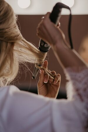 Bride twists the hair with a curling iron at home. Preparation of the bride. Close up. Women doing hairstyle herself and using straightener on beautiful long curl hair. Beauty and haircare concept.