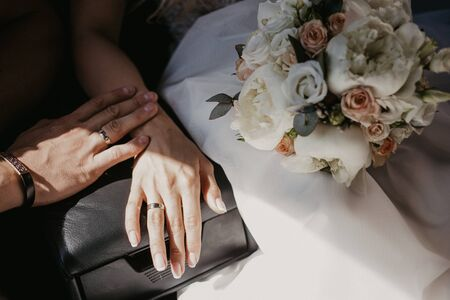 A hand of wedding couple touch each other. Hands newlyweds with wedding rings close up. Bridal hands with rings on black leather armrest on car seats. Shadow because of the sun.