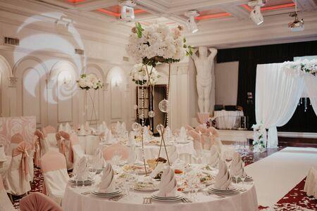 Dekoracje ślubne kwiaty w restauracji. Okrągłe stoły bankietowe, ozdobione bukietem białych kwiatów pośrodku stołów.