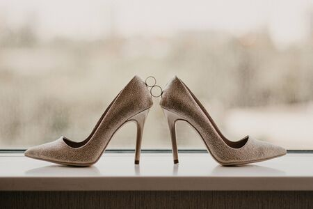 Gold wedding rings between pair of golden high heel shoes. Wedding details on mirror floor near panoramic window.