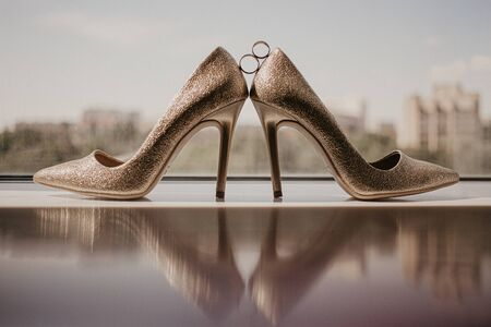 Gold wedding rings between pair of golden high heel shoes. Wedding details on mirror floor near panoramic window. On sunshine. 스톡 콘텐츠