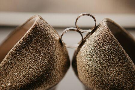 Gold wedding rings between pair of golden high heel shoes. Wedding details on mirror floor near panoramic window. Close up. Macro.