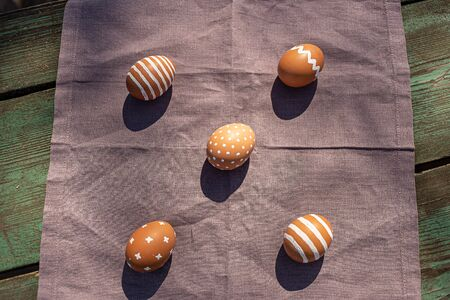Painted 5 five brown eggs with various white patterns for Easter holiday on cotton purple tablecloth with sunlights and shadows. Top view. Eastern European Orthodox cultures. Easter concept.