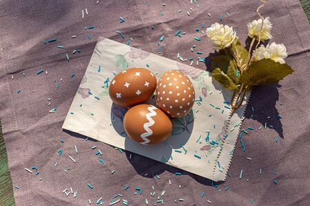 Painted brown eggs with various white patterns for Easter holiday on cotton purple tablecloth with sunlights and shadows. Flower and vintage paper. Decoration blue candies. Top view.