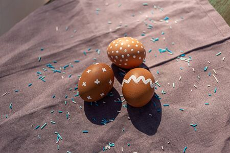 Painted three brown eggs with various white patterns for Easter holiday on cotton purple tablecloth with sunlights and shadows. Decoration blue candies. Side view. Eastern European Orthodox cultures.