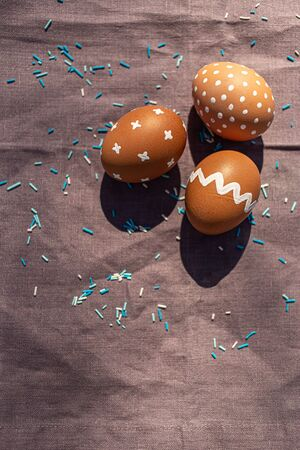 Painted 3 three brown eggs with various white patterns for Easter holiday on cotton purple tablecloth with sunlights and shadows. Decoration blue candies. Top view. Eastern European Orthodox cultures.