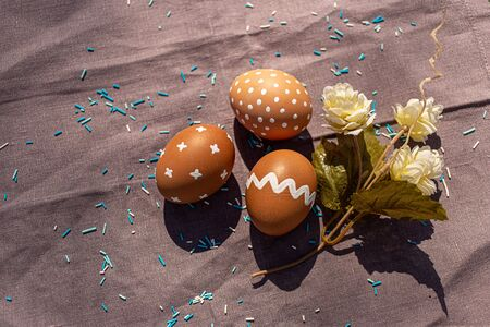 Painted three brown eggs with various white patterns for Easter holiday on cotton purple tablecloth with sunlights and shadows. Decoration blue candies and flower. Eastern European Orthodox cultures. Reklamní fotografie