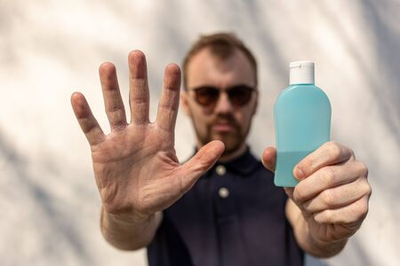 Hand sanitizer alcohol gel rub clean hands hygiene prevention of coronavirus virus outbreak. Man showing one hand and holding a bottle of antibacterial sanitiser soap. Uses On The Street. Reklamní fotografie