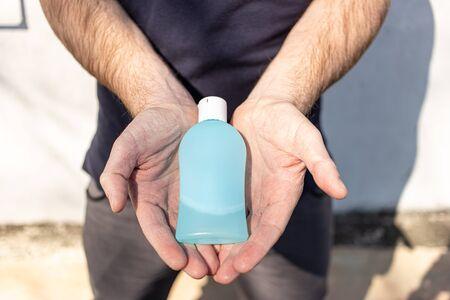 Hand sanitizer alcohol gel rub clean hands hygiene prevention of coronavirus virus outbreak. Man holding bottle of antibacterial sanitiser soap. Outside on the street with sunshine and shadows. Reklamní fotografie