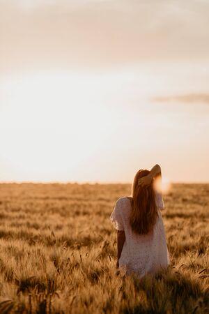 Young beautiful girl enjoying nature on the field. Sunlight rays. Beautiful Teenage Model girl in white dress running on the Field, Sun Light. Glow Sun. Free Happy Woman. Sunset on isolation Reklamní fotografie