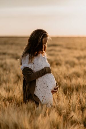 Young beautiful pregnant woman looking down and touching her belly in the wheat orange field on a sunny summer day. Nature in the country. Miracle expectation. Sunset on isolation Reklamní fotografie