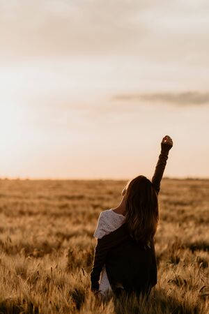 Young beautiful girl in white dress and jacket walking through the wheat orange field on a sunny summer day. Feel freedom with arm stretched to the sky. Nature in the country. Sunset on isolation