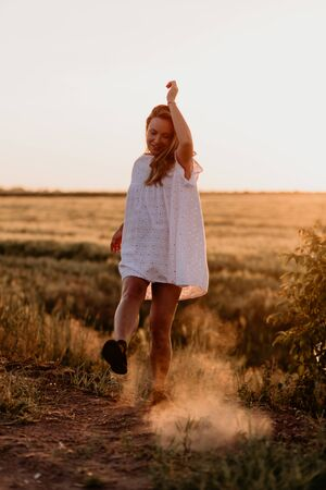 Young beautiful pregnant woman in white dress walking in the wheat orange field on a sunny summer day. Nature in the country. Miracle expectation. Sunset on isolation