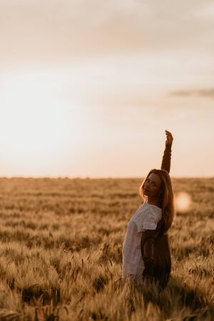 Young beautiful pregnant woman in white dress walking in the wheat orange field on a sunny summer day. Feel freedom with arm stretched to the sky. Miracle expectation. Sunset on isolation. Sun glare 免版税图像
