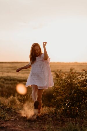 Young beautiful woman making dust with her foot and screaming in the wheat orange field on a sunny summer day. Going crazy. Feeling free and happy. Miracle expectation. Sunset on isolation. Sun glare 免版税图像