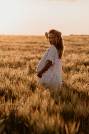 Young beautiful pregnant woman in white dress looking to the side and touching her belly and hairs in the wheat orange field on a sunny summer day. Miracle expectation. Sunset on isolation. 免版税图像
