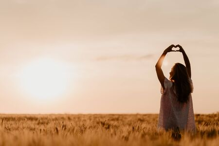 Young beautiful pregnant woman in white dress touching her belly in the wheat orange field on a sunny summer day. Sun glare on sunset. Pregnant woman loving her baby. Making heart symbol in the air