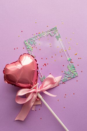 Valentine day concept. Creative layout with balloon made of valentine hearts with pink ribbon bow and blank transparent card certificate with green leaves on pink background. Flat lay, top view