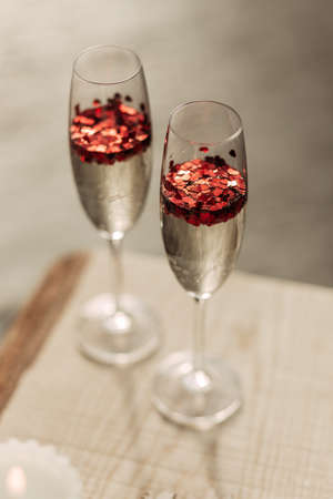 Happy Valentines day celebration concept. Close up of 2 two glasses with sparkling champagne and red heart shaped confetti. Love potion in glass