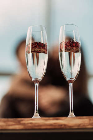 Happy Valentines day celebration concept. Close up of 2 two glasses with sparkling champagne and red heart shaped confetti. Love potion in glass. Loving couple blurred on background