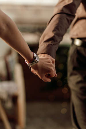 Hands of romantic couple walking happy together indoor in apartment. Close up of holding hands together 免版税图像