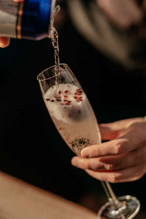 Happy Valentines day celebration concept. Man pouring sparkling champagne in glass with red heart shaped confetti. Love potion in glass. Close up