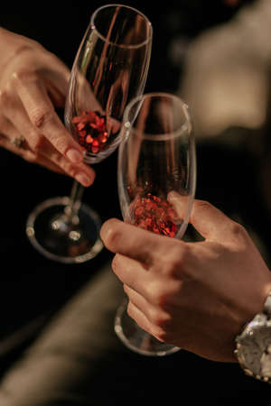 Love couple holding empty champagne glass with red heart shaped confetti. Love potion in glass. Close up 免版税图像