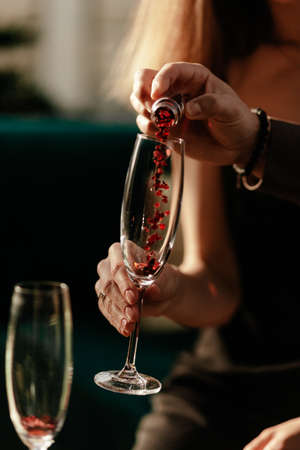 Happy Valentines day celebration concept. Man pouring love potion in womans empty champagne glass. Red Heart shaped confetti in glass. Close up