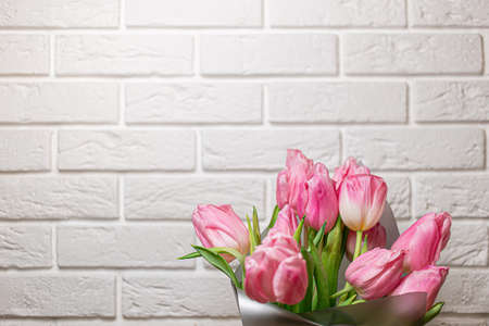 Bouquet of beautiful pink spring tulips in vase on wooden table near white brick wall. Closeup with space for text. Spring greeting card. Concept of international women's day, mother's day, easter.