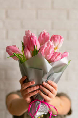 Woman with beautiful pink spring tulips near white brick wall. Closeup with space for text. Spring greeting card. Concept of international women's day, mother's day, easter. Copy space 免版税图像