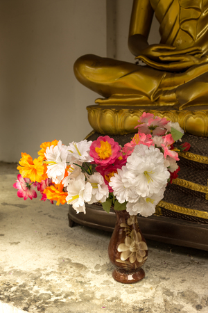 buddha image: flowers offering in order to pay respect  in front of buddha image Stock Photo