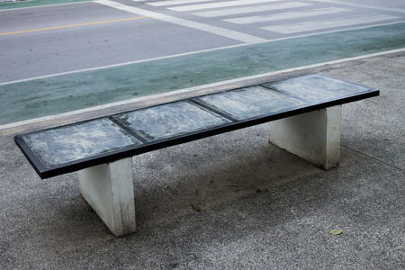 zebra crossing: public chair set up beside the street near zebra crossing.