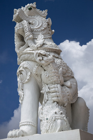 the protector: A lion statue symbolizes to the protector in front of the white cloud. Stock Photo