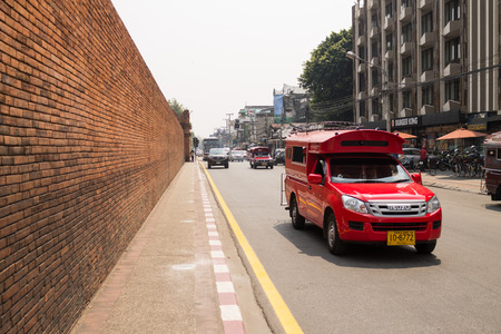 tha: ChiangMai, Thailand. March, 03-2016: The red trucks for renting are driving passby the iconic Tha Phae gate  .