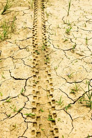 motobike: The motobike trace above cracked and droughty ground simbolizes to hardnessly travel. Stock Photo
