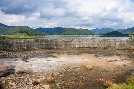 dyke: The inadequacy of water reservoir was shown in its low level at the irrigation dam.
