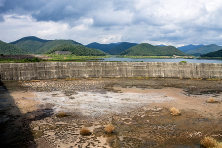 dyke: ChiangMai, Thailand. November, 10-2016: The inadequacy of water reservoir was shown in its low level at the irrigation dam. Stock Photo