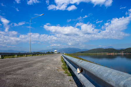 The road leads to the mountain above the irrigation dam. Stock Photo