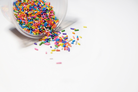 Colorful sugar sprinkle on white background, mess up pouring from clear plastic glass. Sudio soft lighting. Stock Photo