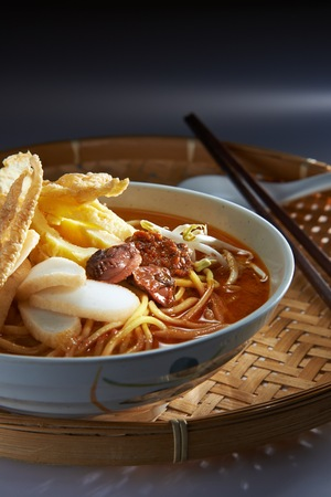 Malaysia favorite spicy noodle laksa with fish cake and cockle