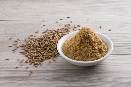 Cumin powder and seeds on wooden texture background
