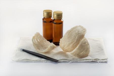 Edible birdnest with essence bottle and pincer on clean background Reklamní fotografie