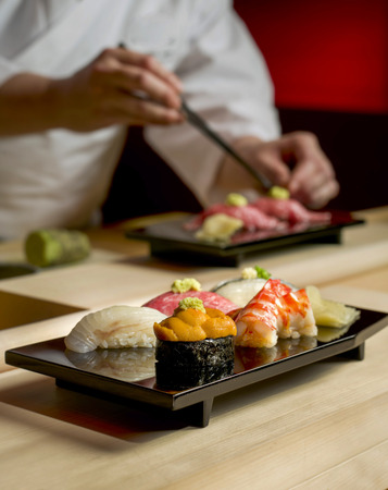 Assorted sushi with sushi chef is preparing another set Stock Photo - 61684599