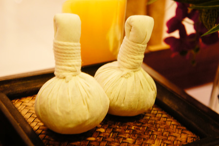 Two Spa herbal compressing balls on a wooden tray