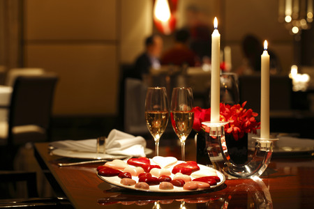 Romantic table setting with Chocolates, Candle and Wine Stockfoto